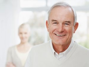 Older man smiling with his wife in the background
