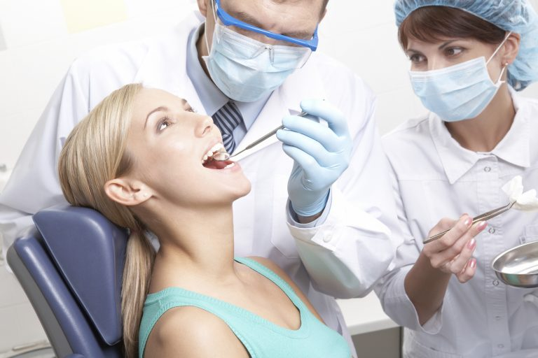 Woman in dental chair with dentist operating on her