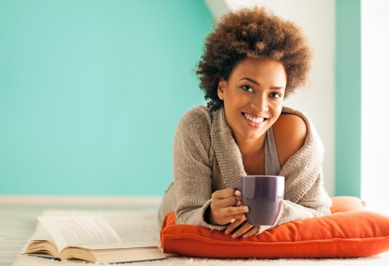 Woman drinking from coffee mug and smiling