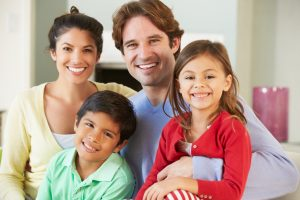 Happy family with two young children smiling