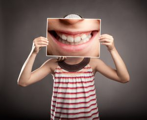 Girl holding large picture of teeth over her face