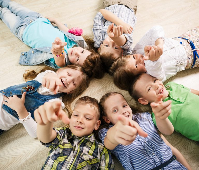 Children sitting in a circle pointing at you